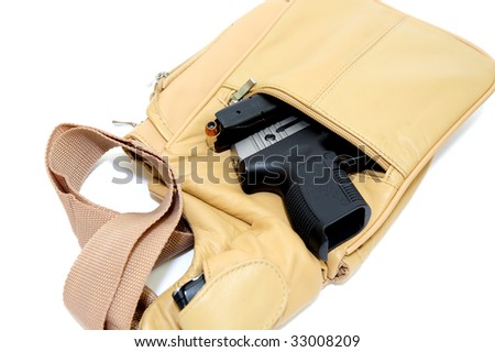 A light brown womens purse with a .45 caliber pistol, the magazine removed showing the hollow point cartridge in detail with a cell phone in the shoulder strap pouch on a light colored background - stock photo