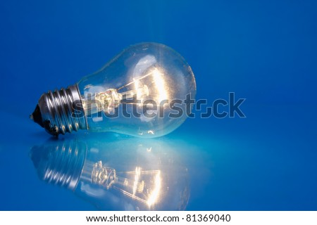 A light bulb isolated on blue background - stock photo