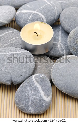 A light candle with pebble on mat