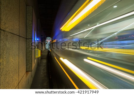A light rail train passing by in an underground transit tunnel creating multi-colored streaks