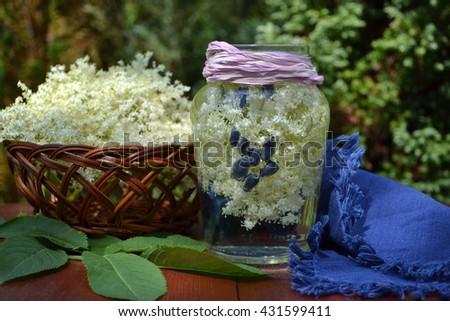 A light, refreshing flavored water  made with fresh seasonal ingredients . Elderflower and berries of honeysuckle. - stock photo