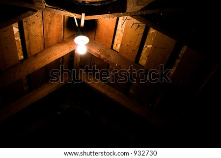 A lightbulb in the ceiling of an attic with nails sticking through the roof and cobwebs