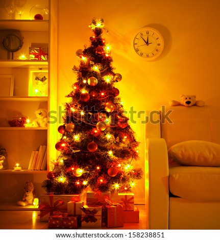 A lighted Christmas tree with presents underneath in living room - stock photo