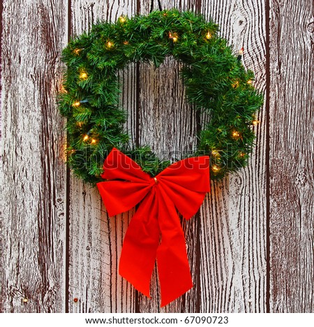 A lighted Christmas wreath with a big red bow hanging outside with room for your text - stock photo