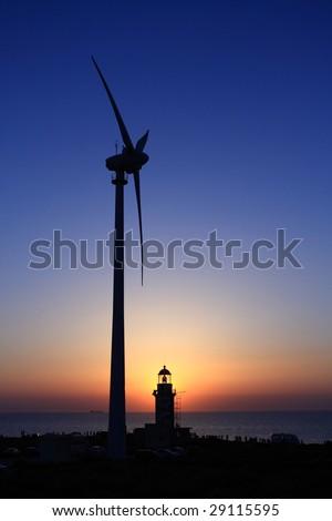 a lighthouse, a wind turbine and a sunset - stock photo