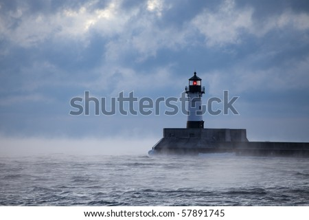 A lighthouse beacon shining in some rough weather. - stock photo