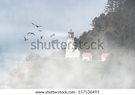 a lighthouse in the fog with birds flying around - stock photo