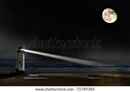 a lighthouse on the coast at night with beam of light and a big bright moon - stock photo
