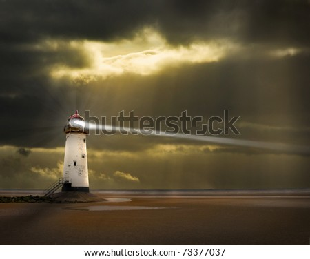 a lighthouse on the welsh coast with light beam and stormy, threatening sky beyond - stock photo