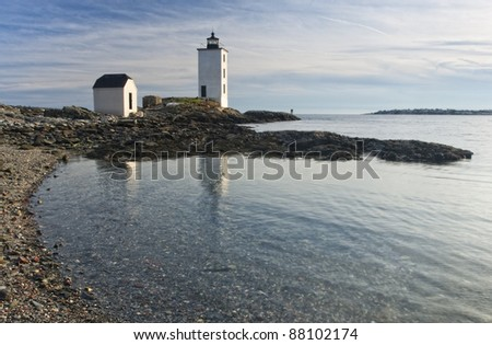 A lighthouse reflection in the calm waters on Dutch Island off Rhode Island. - stock photo
