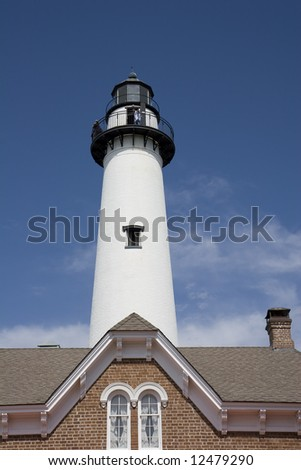 A lighthouse rising into the sky against a blue sky