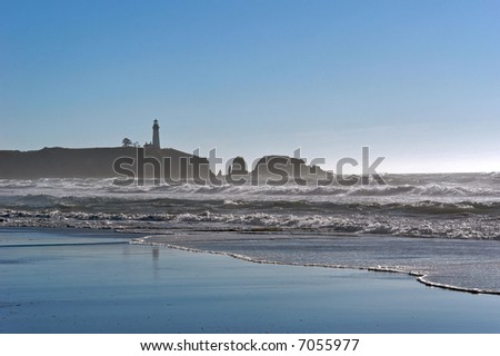 a lighthouse stands tall on the cliff in this timeless image of the American west coast showing the waves crashing on the beach and mist in the background