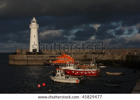 A lighthouse surrounded by bright colored boats against a moody sky