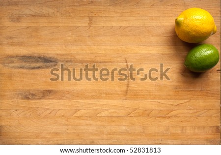 A lime and a lemon sit on a worn butcher block cutting board - stock photo