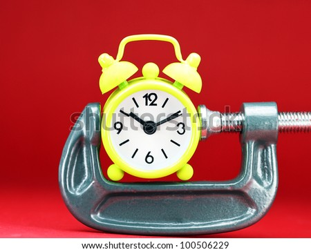A lime green alarm clock placed in a Grey clamp against a pastel blue background, asking the question do you manage your time effectively. - stock photo