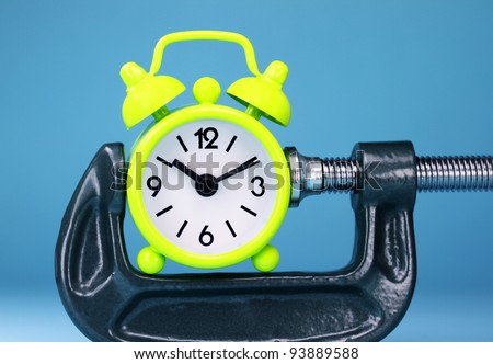 A lime green alarm clock placed in a Grey clamp against a pastel purple background, asking the question do you manage your time effectively - stock photo