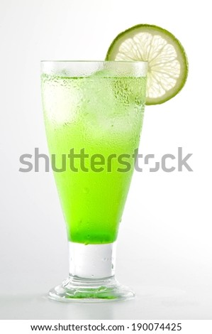 A lime wedge on a glass containing a green drink. - stock photo
