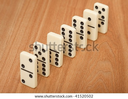 A line from seven dominoes on a wooden surface