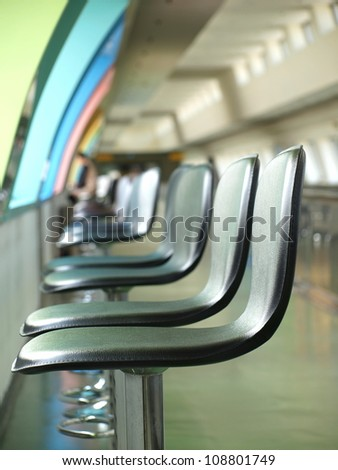 A line of bar stools inside a public building - stock photo