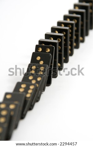 A line of black dominoes falling down, isolated on a white background with a narrow depth of field.