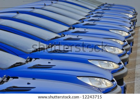 A line of cars, all the same,  parked side by side - stock photo