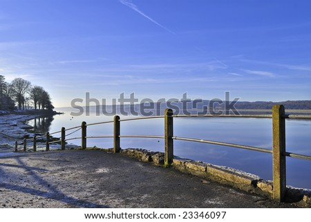 A line of fenceposts at Arnside shore, Cumbria, North West England - stock photo