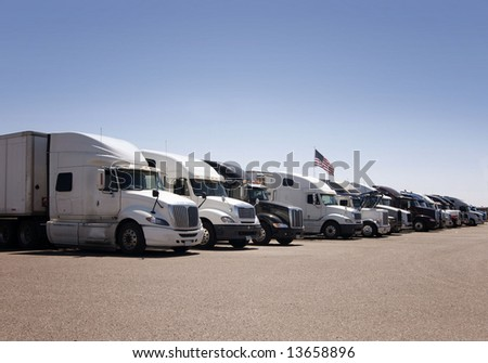 A line of heavy duty freight trucks parked in a row at an American highway truck stop - stock photo