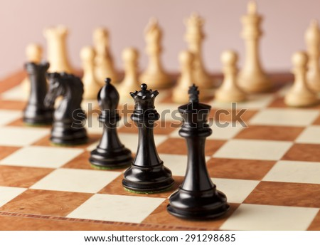 A line of luxurious black Staunton chess pieces carved in genuine ebony wood standing on elm burl and bird's eye maple superior traditional chessboard facing the white army of chess pieces before game - stock photo