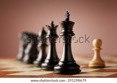 A line of luxurious Staunton chess pieces carved in genuine ebony wood facing a single white pawn made of natural boxwood standing on elm burl and bird's eye maple superior chessboard in focus - stock photo