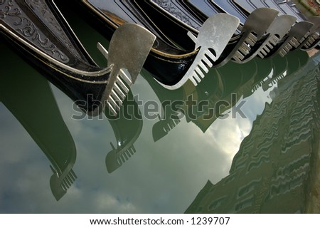A line of moored gondolas in Venice, their bow decorations reflected in the still waters of the canal. - stock photo