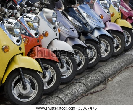 A line of mopeds/scooters, gleaming and shiny.  They look as if they are ready to go.