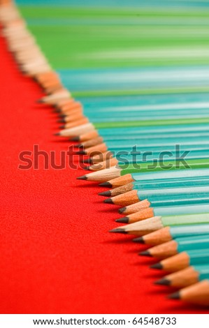 A line of pencils on red backgrounds - stock photo