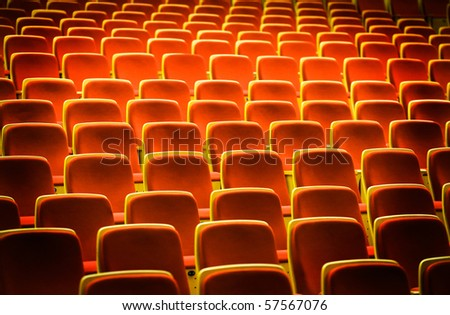 A line of red theater chairs. - stock photo