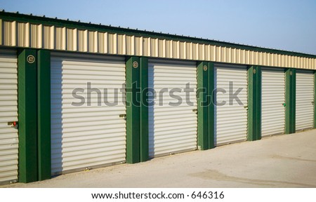 A line of rental storage units with roll-up corrugated metal doors.
