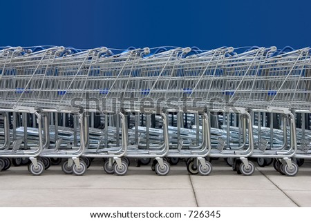A line of shopping carts against a blue wall. - stock photo