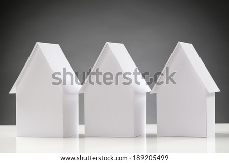 A line of three identical white houses on a white surface with a dark background. - stock photo