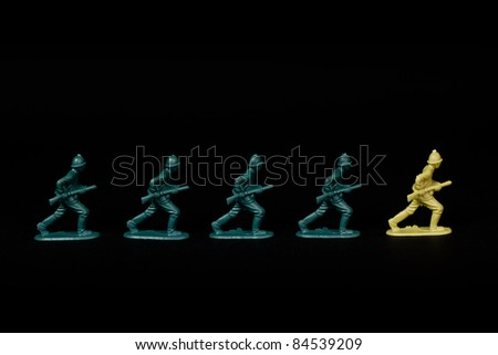 A line of toy soldiers stood against a black background. They are marching in line with a soldier from the opposition leading them. Conceptual Image with a nice strong contrast.