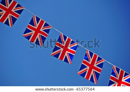 A line of Union Jack flags, stretched across a clear blue sky. Space for text either side of the flags - stock photo