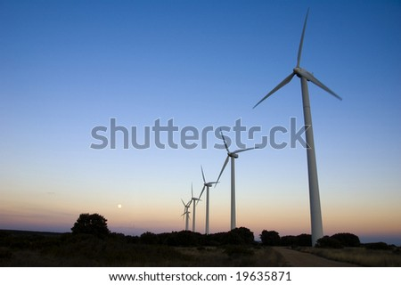 a line of windmills at sunrise
