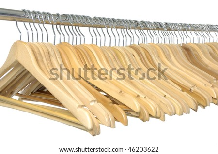 A line of wooden coat hangers on a clothes rail - stock photo