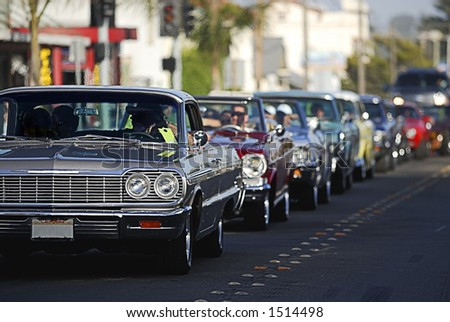 A line up of classic old cars cruising the local strip.