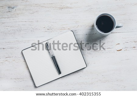 A lined notebook for notes is placed on a table in white lacquered wood, with a pen to write and a cup of coffee, the pages are blank, no writing and no drawings. Top view - stock photo