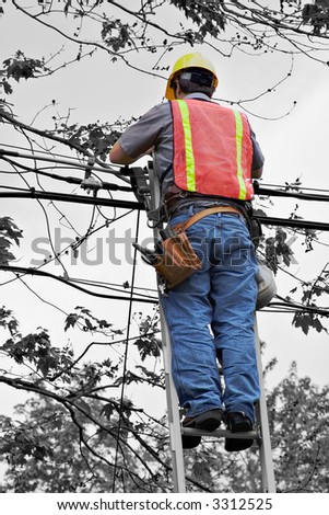 A lineman working on cable - telephone pole from ladder.  Selective color. - stock photo