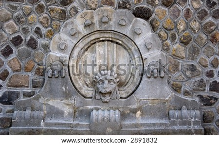 A lion's head in the middle of a stone wall - good for background - stock photo