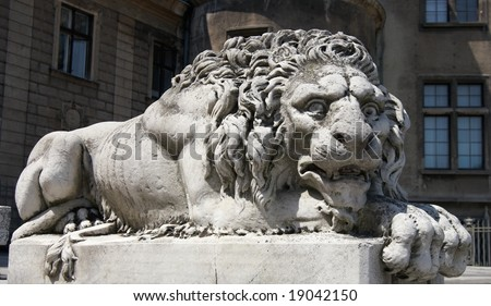 A lion statue sits majestically on it's pedestal outside of the castle Moszna in Poland - stock photo