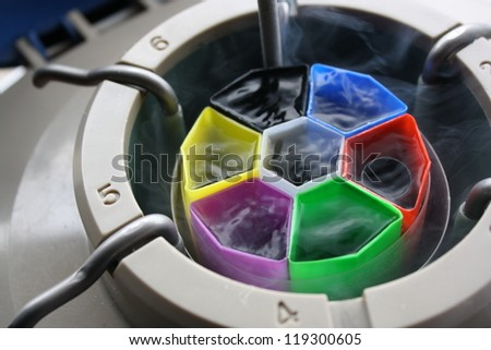 A Liquid Nitrogen bank with a canister with goblets and coloured inserts - stock photo