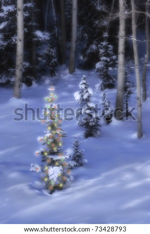 A lit Christmas tree at the edge of a forest on a snowy hillside at dusk - stock photo