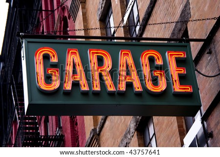 A lit garage neon sign in an urban setting. - stock photo