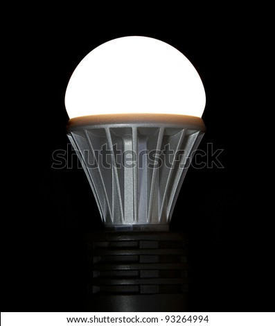 A lit LED bulb isolated on a black background - stock photo