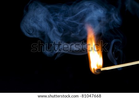 A lit match with an orange flame and blue smoke